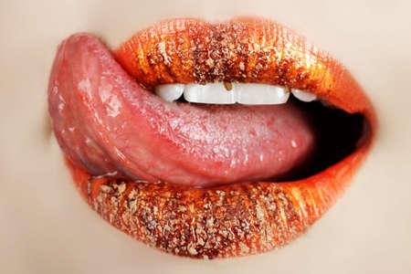 labbra sensuali: Macro di arancione il make-up sulle labbra con la lingua a leccare via il cioccolato in polvere  Archivio Fotografico