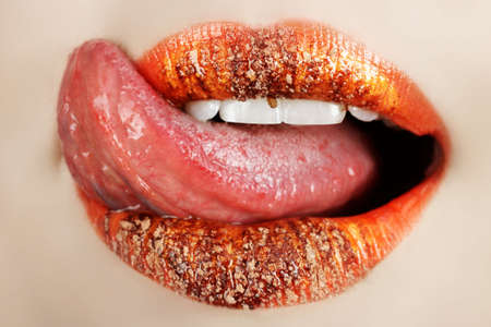girl tongue: Macro of bright orange make-up on lips with tongue licking off chocolate powder  Stock Photo
