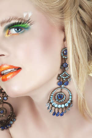 Beautiful blond woman with bright orange lips and false feather lashes in diamante chandelier earrings Stock Photo - 3471382