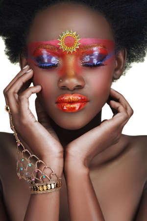 touching noses: African beauty with glossy and golden make-up holding her face in her hands  Stock Photo