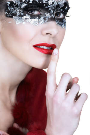 beautiful woman in silver leaf and black mask, holding finger next to her red lips