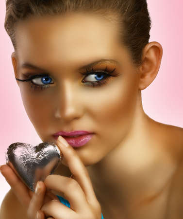 beautiful blond woman with long false lashes holding a silver chocolate heart