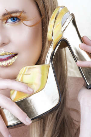 blond woman with blue eyes and long feather false eyelashes holding a high heel shoe. Moist skin with water texture around lips  photo