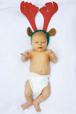 nappy new year: little baby boy in disposable diaper on cotton blanket with reindeer Christmas hat