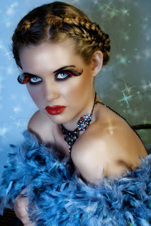 beautiful blond fashion model with feathers and long false lashes on star background Stock Photo - 4241400