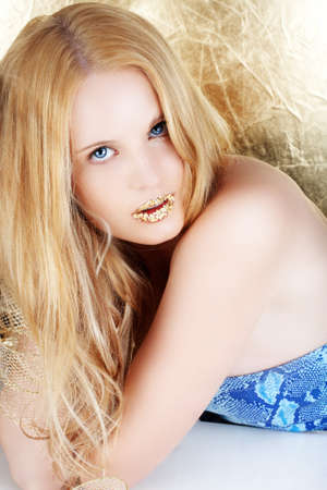 Beautiful young blond woman with long hair and gold leaf lips on golden background