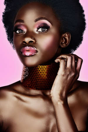 beautiful south African woman with bronze necklace and natural make-up, long false eyelashes, with lots of shine on her skin photo