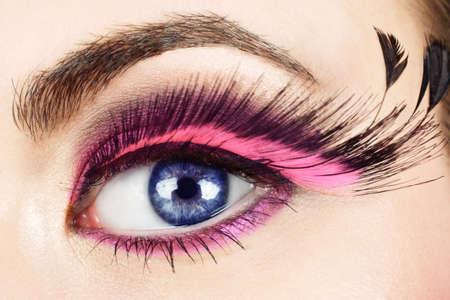 Macro of womans eye with long pink feather fake eyelashes.