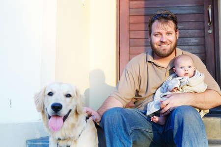 front porch: padre, hijo y el beb� sentado con su perro en el porche de la tarde el sol, se centran en el padre
