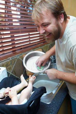 joven lavar los platos con una sonrisa mientras que un niño lo mantiene la empresa en una silla.