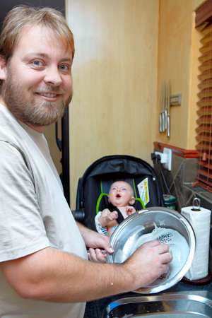household chores: young man washing the dishes with a smile while a baby boy keeps him company in a chair.