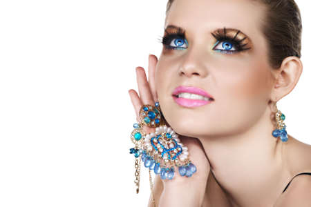 earring: Blond woman with long false lashes holding pearl and blue stones golden jewelry with happy expression . Stock Photo