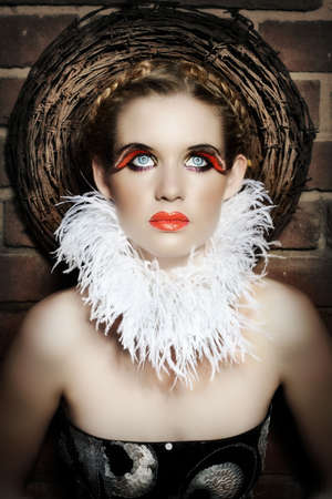 Gothic beautiful woman with feather necklace and false lashes wearing red lips. photo