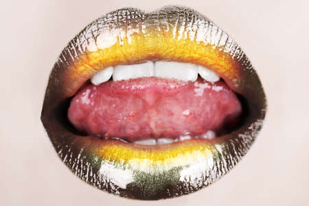 macro of woman sticking her tongue with black glossy lipstick and gold powder shine .