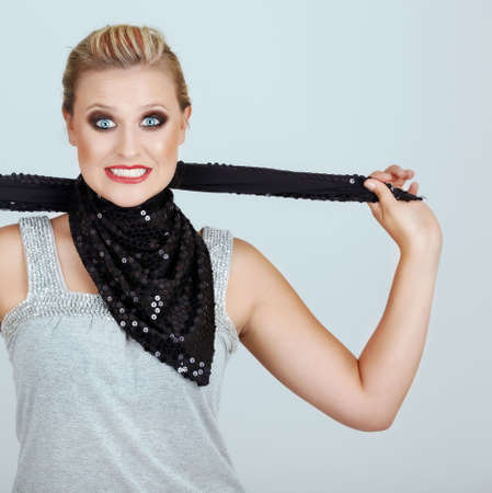 strangling: Fashion victim: young woman with stressed expression strangling herself with a sequence scarf. Stock Photo