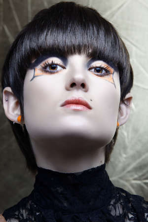 advantaged: Emo girl with straight fringe bob and alternative make-up, piercings on lip and ear from 16bit RAW. Stock Photo