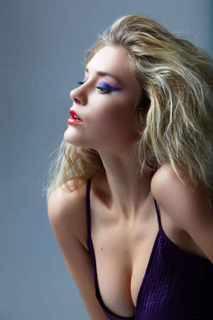 Blond woman with red lips and cat eyes make-up in purple dress. Edited from 16bit RAW in ProPhoto RGB Stock Photo
