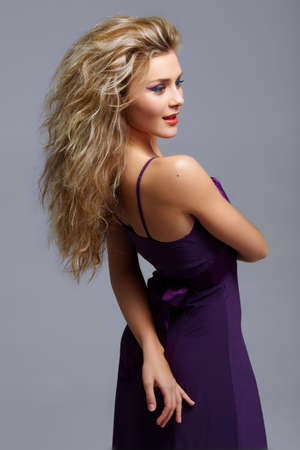 Blond woman with red lips and cat eyes make-up in purple dress. Edited from 16bit RAW in ProPhoto RGB. Stock Photo