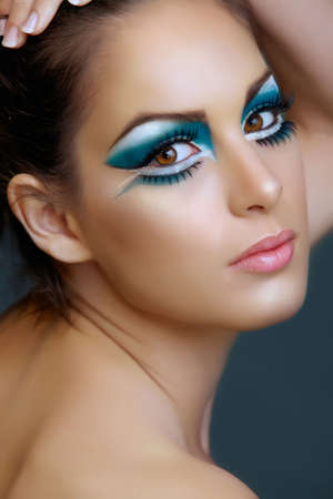liner: Beautiful brunette woman with cat eyes make-up in turquoise and white, from 16bit RAW.