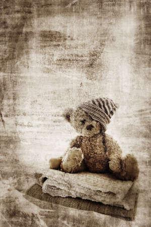 vintage teddy bears: Grunge background con pelliccia orsacchiotto in cappello a mano, seduta su unioni e spazio per il testo.