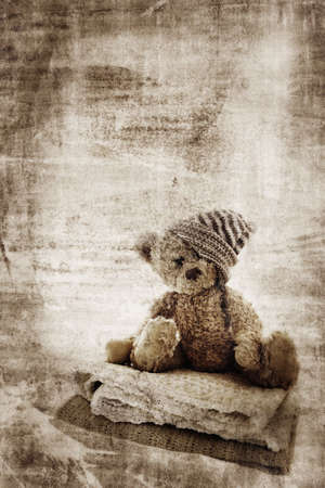 wallpaper wall: Grunge background with fur teddy bear in handmade hat, sitting on quilts and space for text. Stock Photo