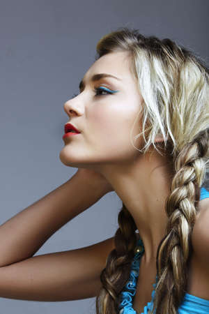 beautiful young woman in turquoise dress with long blond braids. photo