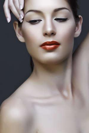collo: bella donna naturale con false ciglia e make-up classico con corallo rossetto