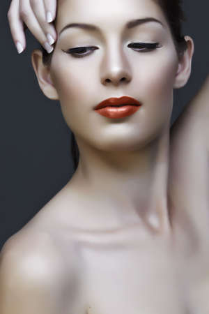 beautiful natural woman with false lashes and classic make-up with coral lipstick