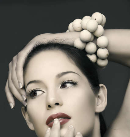 beautiful brunette woman with classic make-up and wooden beads on her hand in vintage finish