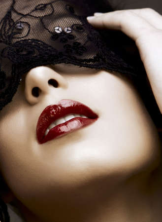 beautiful woman with red lips and lace mask over her eyes. Stock Photo