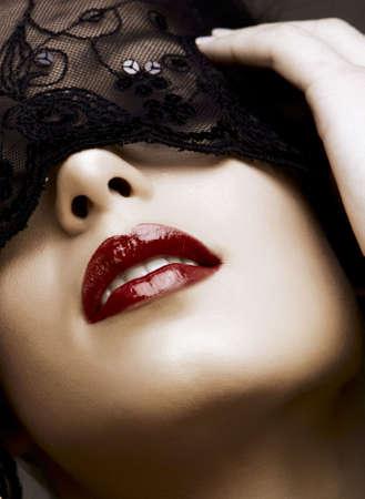 hermosa mujer con labios rojos y máscara de encaje sobre sus ojos.