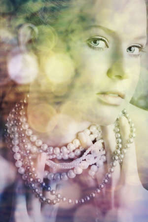 beautiful woman with blue eyes in pearl necklace with bokeh lights - nearest eye in perfect focus. photo
