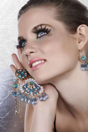 aretes: Mujer rubia con falso larga pesta�as celebraci�n de piedras de perlas y azules joyas de oro con feliz expresi�n de 16 bit RAW.