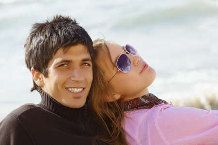 young turkish happy couple on the beach sitting back to back together photo