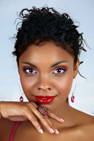 beautiful African woman with red lips and pink eyeshadow, black curly hair pulled back