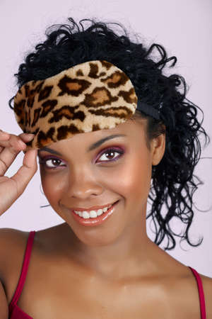 beautiful African woman with natural lips and pink eyeshadows wearing a leopard print sleeping mask over long curly hair photo