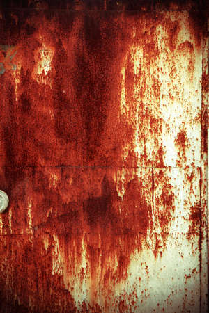 grunge metal door with rusted peeling paint in deep red and blue colour photo