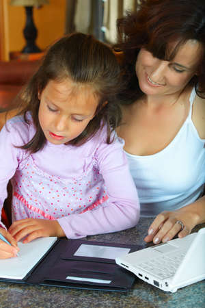 mother helping her daughter with home work photo
