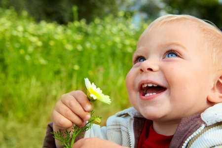 small baby boy holding a daisy in his hand and laughing in the field of flowers.
