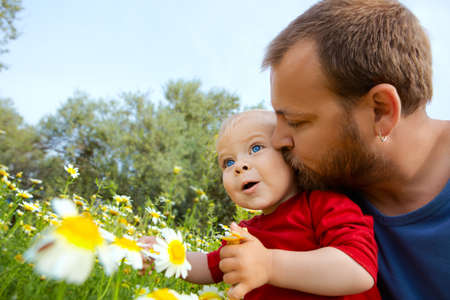 early thirties: father in early thirties gives his son a kiss on the cheek in the flower field  Stock Photo