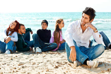 beach hunk: group of Turkish student friends sitting on the beach