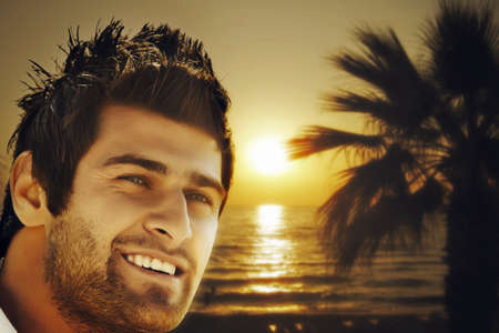 young happy Turkish man on the sunset beach with a palm photo