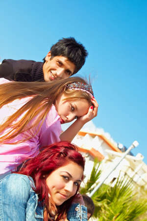 three young friends on a sunny day against blue sky photo