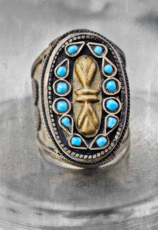 over 100 years old antique Turkish tribal ring with grunge pattern and blue stones on textured background. photo