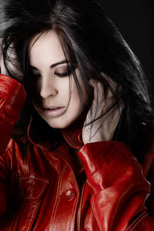 Fashion photo of a beautiful woman with purple smoky eyeshadow touching her black hair, in red leather jacket. photo