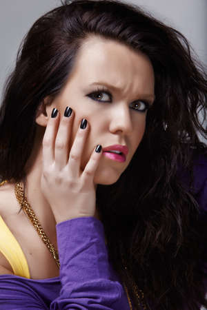 worried young woman with long black hair and black nails with fashion make-up, from 16 Bit RAW. photo