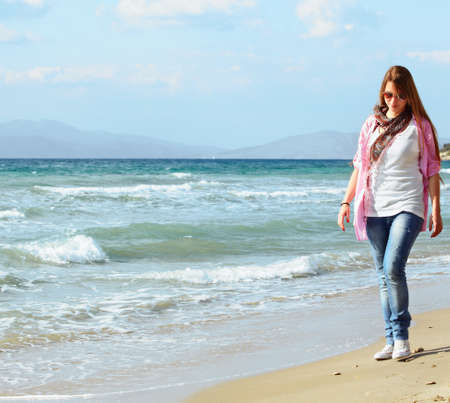 beautiful young teen girl wearing jeans and white top walking on the beach by the blue sea. photo