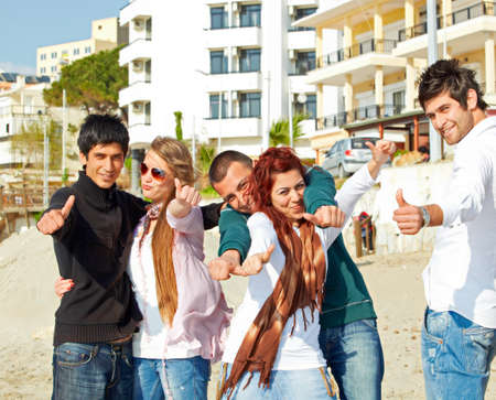 Fun Turkish student friends showing thumbs up in dynamic poses on the beach . photo