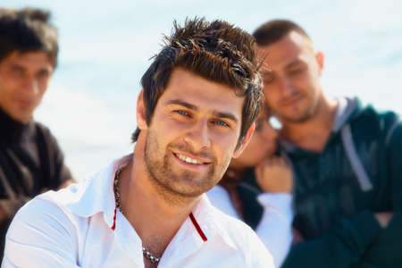 mullet: Turkish young man with mullet hairstyle in white shirt with his friends outdoors.