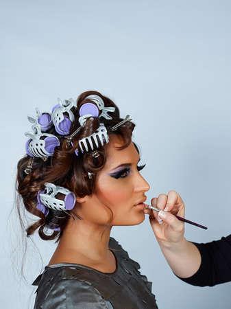 schöne junge Latino-Modell mit Ihrem Haar in Lockenwickler und Make-up getan bevor Mode-Shooting, with Space for text Standard-Bild